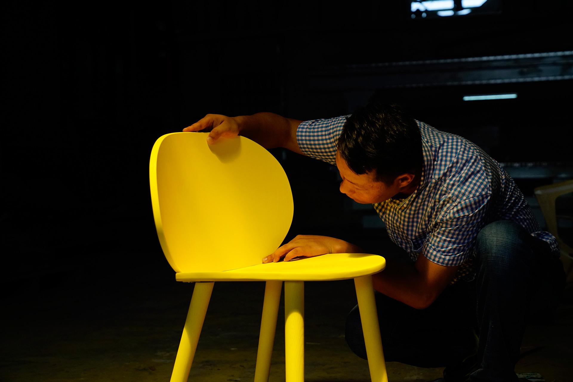 工作人员精细检查椅子的背部细节及连接紧密度