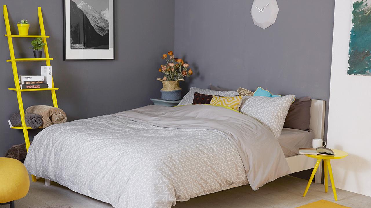 如果床和床品过于朴素,可以从床头柜改善,我们把柠檬黄的画板三角彩几作为床头柜使用,马上让纯色床品不再单调。