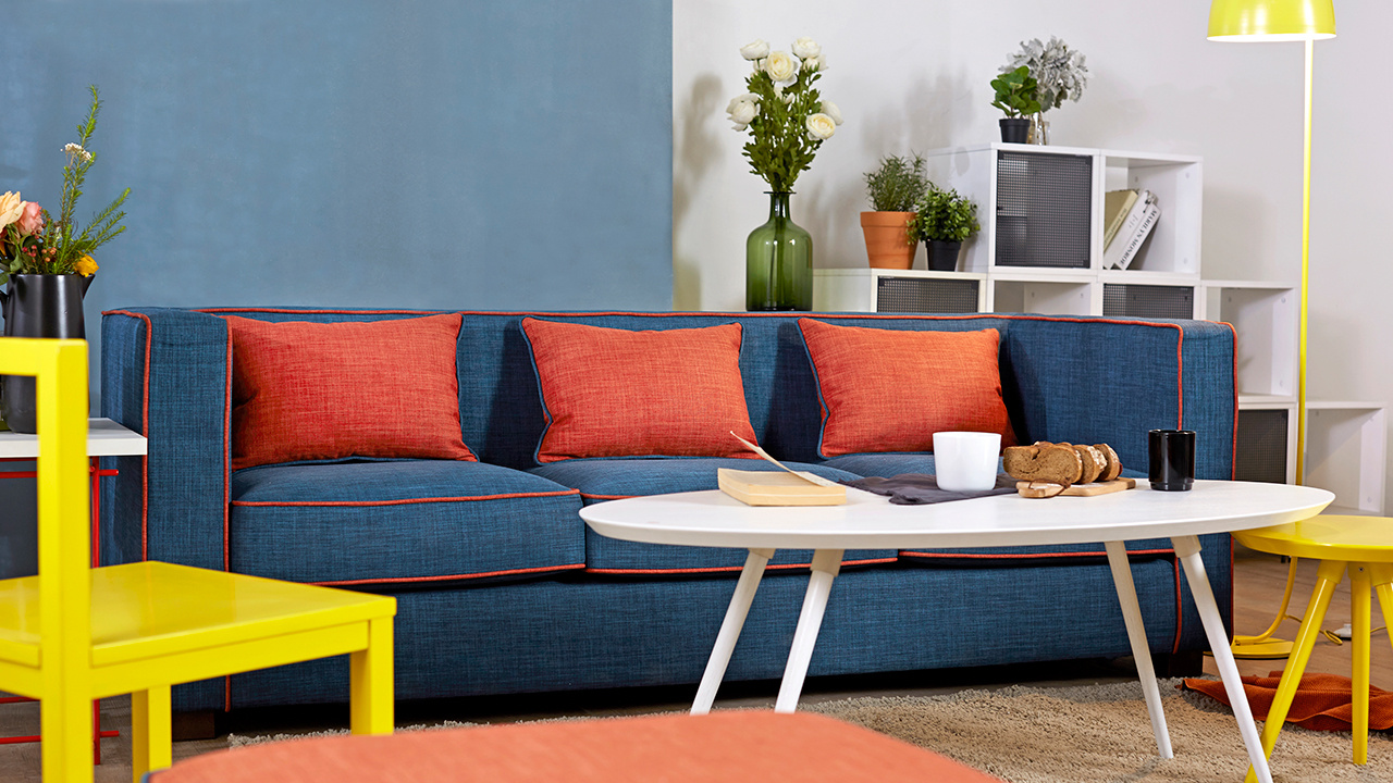 三人座的作业本沙发-岚蓝款奠定了客厅的主色调,蓝色软包与红色抱枕对撞带来沉重又不沉闷的客厅氛围。